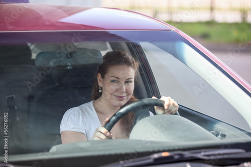 Smiling woman holding wheel and looking through the windscreen