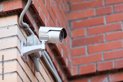 Video surveillance camera in courtyard on brick wall
