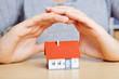Hände schützen Haus wie eine Versicherung