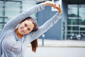 Frau macht Dehnübungen vor dem Sport