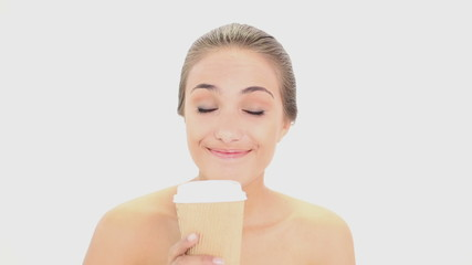 Beautiful model drinking from disposable cup
