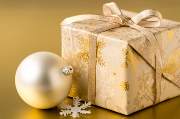 Christmas present and bauble on gold background