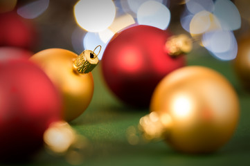 Gold and red christmas baubles on green