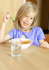 Kleines Mädchen isst Nudeln mit Tomatensoße