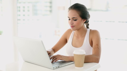 Beautiful young woman using her laptop