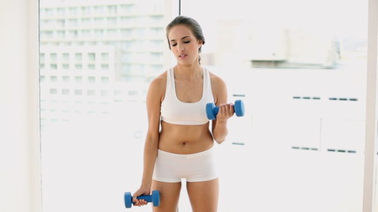 Fit young woman lifting dumbbells and laughing