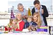 Kind pustet Kerze aus bei Geburtstagsfeier