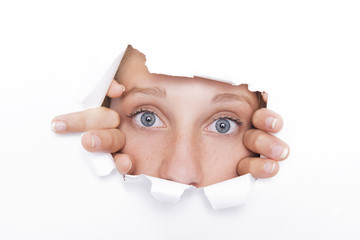 Young woman looks through a hole