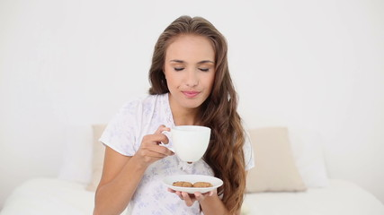 Young woman drinking a cup of tea with cookies