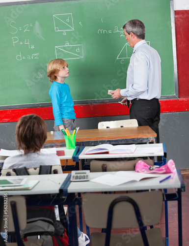 Schoolboy And Teacher Standing By Board In Classroom