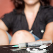 Syringe and female drug addict sitting on the background
