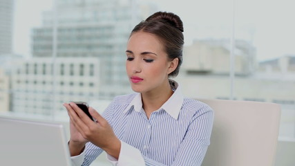 Young businesswoman sending a text at her desk