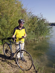 Senior man is riding his old bike on the Danube dike.