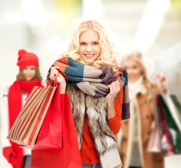 teenage girls in winter clothes with shopping bags