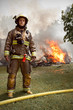 Real Firefighter with house on fire in background - 56285849