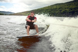 Happy handsome man wakesurfing in a lake