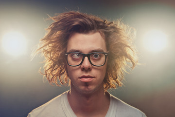 Funny Squinting man with Tousled brown hair in studio