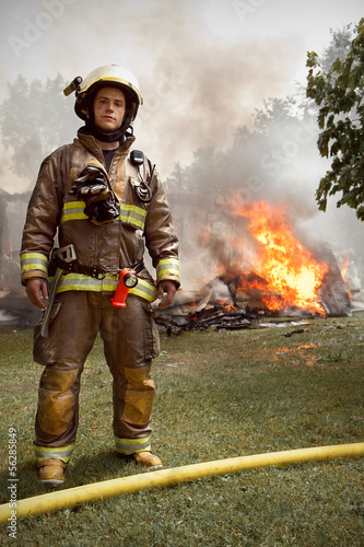 Real Firefighter with house on fire in background