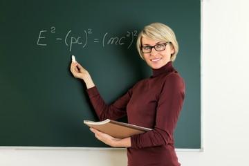Lehrerin steht an Tafel und schreibt