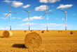 Straw bales on farmland with wind turbines