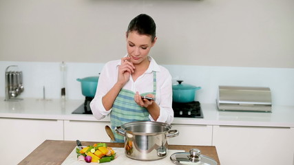 Beautiful brunette sending a text while making dinner