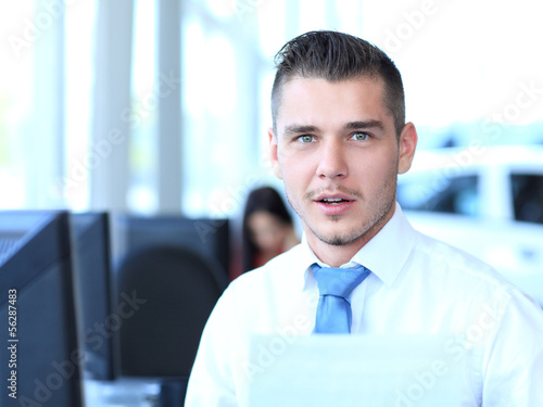 Happy businessman sitting in office