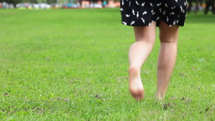 Woman in dress and barefoot jumping on green grass