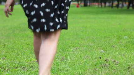 Woman in dress and barefoot running on green grass