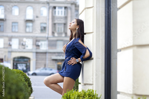 Sexy woman in a blue dress on the street