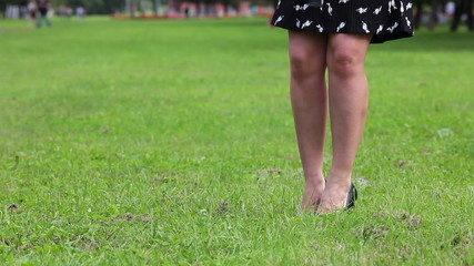 Woman in dress take off her shoes and walking on green grass