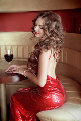 Rich slim beautiful girl sitting at the table holding vine glass