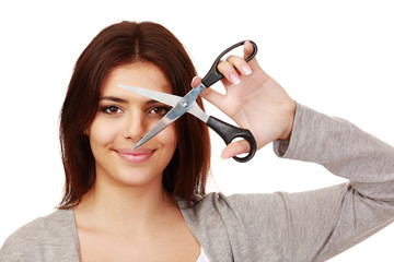 Smiling attractive woman with scissors in front of her face