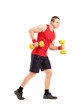 Full length portrait of a muscular athletic man lifting dumbbell