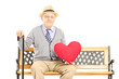 Senior man sitting on a wooden bench and holding a red heart