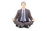 Young businessman in suit sitting on a floor and meditating