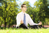Young businessperson with eyeglasses meditating seated in park