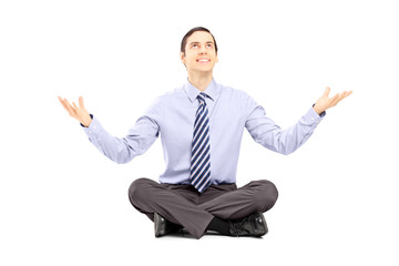 Young businessman sitting on a floor and gesturing with his hand