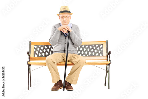 Sad senior man with a cane sitting on a wooden bench