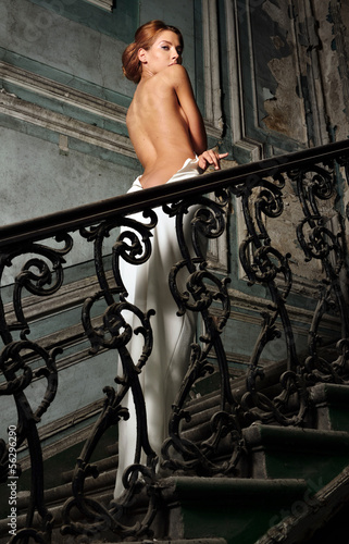 beautiful woman in white dress with naked back in palace. © Dmitriy Raykin
