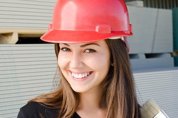 Beautiful girl wearing a red safety helmet on construction site