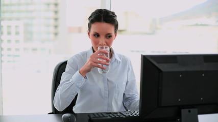 Businesswoman drinking water at her desk