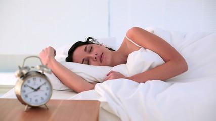 Brunette being woken by her alarm clock in bed