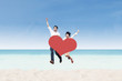 Asian couple jumping on beach with heart card
