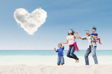Asian family jumping under heart cloud