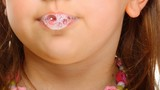 Close up little girl doing fun saliva bubbles