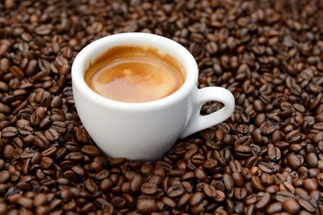 Coffee beans with white cup espresso.