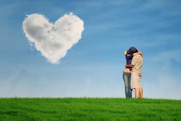 Couple kissing under heart shape cloud