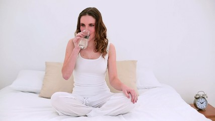 Pretty model sitting on bed drinking glass of water