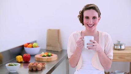 Pretty model standing in kitchen drinking mug of coffee