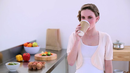 Pretty model drinking disposable cup of coffee